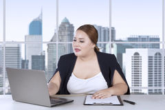 Fat woman working on laptop and clipboard Royalty Free Stock Image