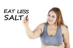 Fat woman writes eat less salt word. Portrait of fat woman writing eat less salt word in the studio, isolated on white background Stock Image