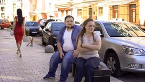 Fat woman angry at boyfriend looking at pretty lady passing by street, conflict. Fat women angry at boyfriend looking at pretty lady passing by street, conflict stock images