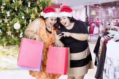 Fat  women with Santa hat and smartphone Royalty Free Stock Images