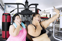 Fat women with smartphone in the fitness center Royalty Free Stock Images