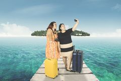 Fat women taking a photo in the jetty Stock Image