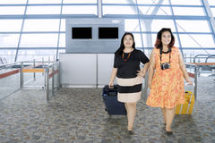 Fat women walking in the airport terminal. Image of two fat women carrying suitcase while walking in the airport terminal Royalty Free Stock Photos