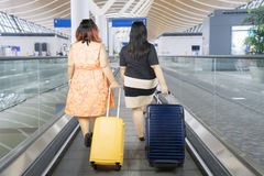 Fat women walking on the escalator airport. Back view of two fat women carrying a suitcase while walking on the escalator airport Stock Images