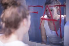 Fat writing on mirror. Fat red writing on mirror and teenage girl Royalty Free Stock Photo