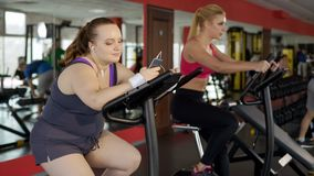 Fat young woman using fitness mobile app while training to lose weight in gym stock image
