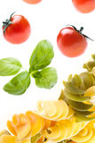 Fatal Attraction. Tomatoes and basil falling on fusilli Stock Photos