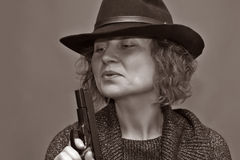 The fatal woman. The woman of average years in a black hat with a pistol Stock Image