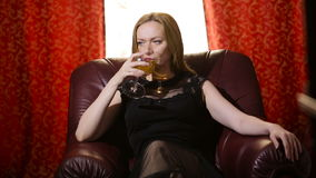 A fatal woman in a black dress and a red lipstick on her lips sits in a leather armchair with a glass of white wine and