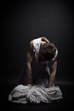 Fatality. The young man in a female dress over the plaster cast wrapped by a white fabric Stock Photography
