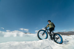 Fatbike (fat bike or fat-tire bike). Fatbike (also called fat bike or fat-tire bike) - Cycling on large wheels. Extreme girl riding a bike on snow melted ice Stock Photography
