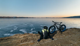 Fatbike fat bike or fat-tire bike. Fatbike also called fat bike or fat-tire bike - Cycling on large wheels. Traveller cyclist sits on a hillside. He is resting royalty free stock images