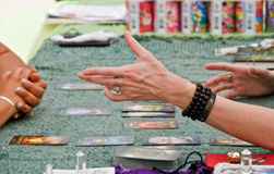 About fate. A pair of hand stretching out over a table with taro card display. Crystal and taro card deck on the side stock photos