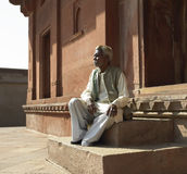 Fatehpur Sikri - India. Old man resting on the steps of the Diwan-i-khas in Akbar's Citidel of Fatehpur Sikri near Agra in the Uttra Pradesh region of Northern Stock Photography