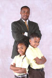 Fater and kids. A successful father posed with his two school aged kids Stock Image