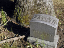 Father. A simple grave marker at the foot of a tree. The tree was probably a sapling when this person was buried a hundred years ago Stock Photo