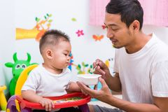 Father acting Mom feeding his son baby 1 year old on chair. In the house royalty free stock images