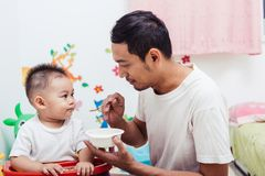 Father acting Mom feeding his son baby 1 year old on chair. In the house stock images