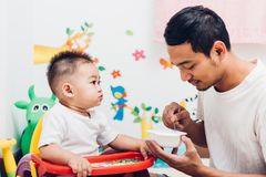 Father acting Mom feeding his son baby 1 year old on chair. In the house royalty free stock photo