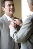 Father adjusting groom`s tie, smiling, low angle view Stock Image