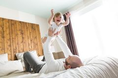 Father with adorable baby toddler on bed. A Father with adorable baby toddler on bed Royalty Free Stock Photography