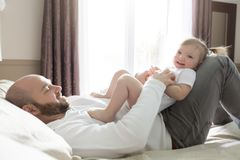 Father with adorable baby toddler on bed. A Father with adorable baby toddler on bed Royalty Free Stock Photo