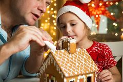 Father and adorable daughter in red hat building Christmas gingerbread house royalty free stock photos