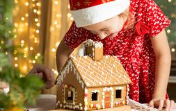 Father and adorable daughter in red hat building Christmas gingerbread house royalty free stock images