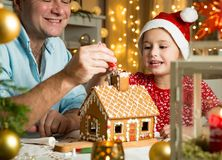 Father and adorable daughter in red hat building Christmas gingerbread house stock photo