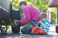 Father and adorable little boy repairing car and changing wheel Royalty Free Stock Image