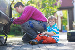 Father and adorable little boy repairing car and changing wheel Royalty Free Stock Images