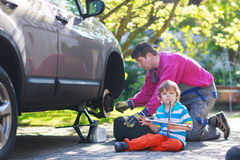 Father and adorable little boy repairing car and changing wheel Royalty Free Stock Photos