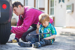 Father and adorable little boy repairing car and changing wheel Stock Image