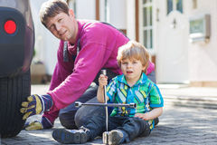 Father and adorable little boy repairing car and changing wheel Stock Photos