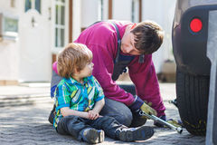 Father and adorable little boy repairing car and changing wheel Stock Images