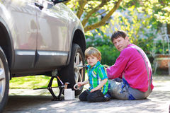 Father and adorable little boy repairing car and changing wheel Stock Photography