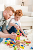 Father and adorable son playing with constructor on floor at home. Family fun at home concept Royalty Free Stock Photo