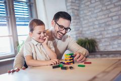 Father and adorable son playing with education game stock photos