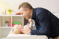 Father adoring his beautiful baby daughter. In her room Royalty Free Stock Photos