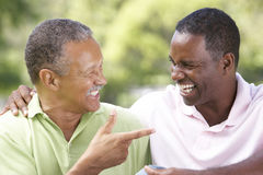 Father With Adult Son In Park. Laughing At Joke Stock Images