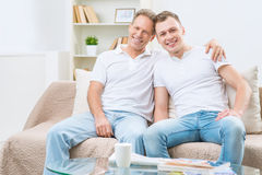 Father and adult son sitting on the sofa. Best friends. Happy positive vivacious father and adult son sitting in the sofa and bonding to each other while stock photos
