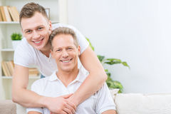 Father and adult son sitting on the sofa Stock Photo