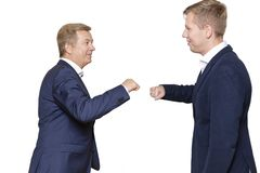 Father with adult son stand back to back, smiling. Isolated on white background royalty free stock photos