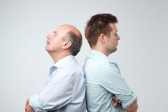 Father with adult son standing back to back royalty free stock photo