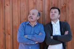 The father and the adult son are standing by the wooden wall and looking thoughtfully upward. Royalty Free Stock Image