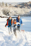 Father And Children Pulling Sledge Up Snowy Hill Royalty Free Stock Photo