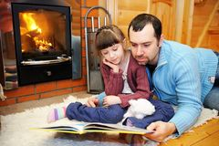 Father And Daughter Reading In Front Of Fireplace Royalty Free Stock Image
