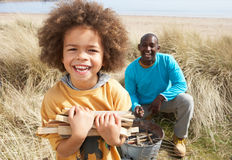 Father And Son Collecting Firewood On Beach Royalty Free Stock Photography