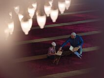 Free Father And Son In Mosque Praying And Reading Holly Book Quran Together Stock Photos - 181915323