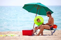 Father And Son Relaxing On Sea Beach Stock Photo